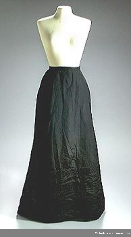 Svart lång kjol med sydda veck framtill. Nertill påsydda band 3x3 st.Breddmåttet anger midjemåttet.Ägarinnan till kjolen, Alma Ringqvist var bosatt i Vadstena, född 12/6 1862, död 28/6 1954. Hennes far var den förste chefen för Vadstena Sparbank.Alma själv gick postexpeditörskurs i Stockholm 1886-87. Hon tjänstgjorde i Arboga fram till sin pensionering 1922. Hon var även verksam vid museet i Vadstena och donator.