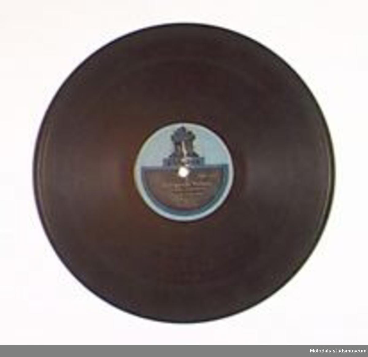 En sk stenkaka. Musik ena sidan: Skärgårdsvalsen (Anselm Johansson) Danse Orkester Sándor Jòzsi A149856.Musik andra sidan: Veronika Shimmy (H Tichauer) Danse Orkester Sándor Jòzse A143857.Märkt: Odeon Be 3026 H. 3 Be 3023 H.3.Repad.Förvaras i MM01476 (skivalbum).Stenkakor tillverkades av konstharts (plast av bl a kåda) och skiffermjöl (eller annat fyllnadsmjöl).