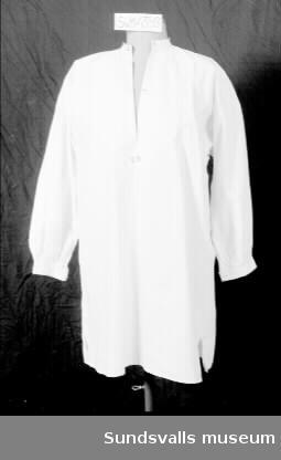 Vit skjorta med vida ärmar som rynkats ihop vid manschetten, vilken knäpps med en silverfärgad knapp. Rund hals. Sprund. Mörkrosa broderat monogram vid sprundets slut.