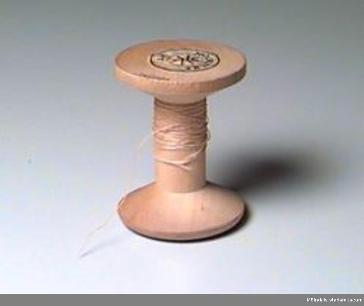 """Runda pappersetiketter på båda sidor av den obehandlade trärullen. Den ena i rött/rosa/silver på vitt, den andra i svart på vitt. Text på etiketterna: """"MÖLNLYCKE VIT/MÖLNLYCKE 200 METER 4 m/g"""". Lite gulnad tråd kvar på rullen."""