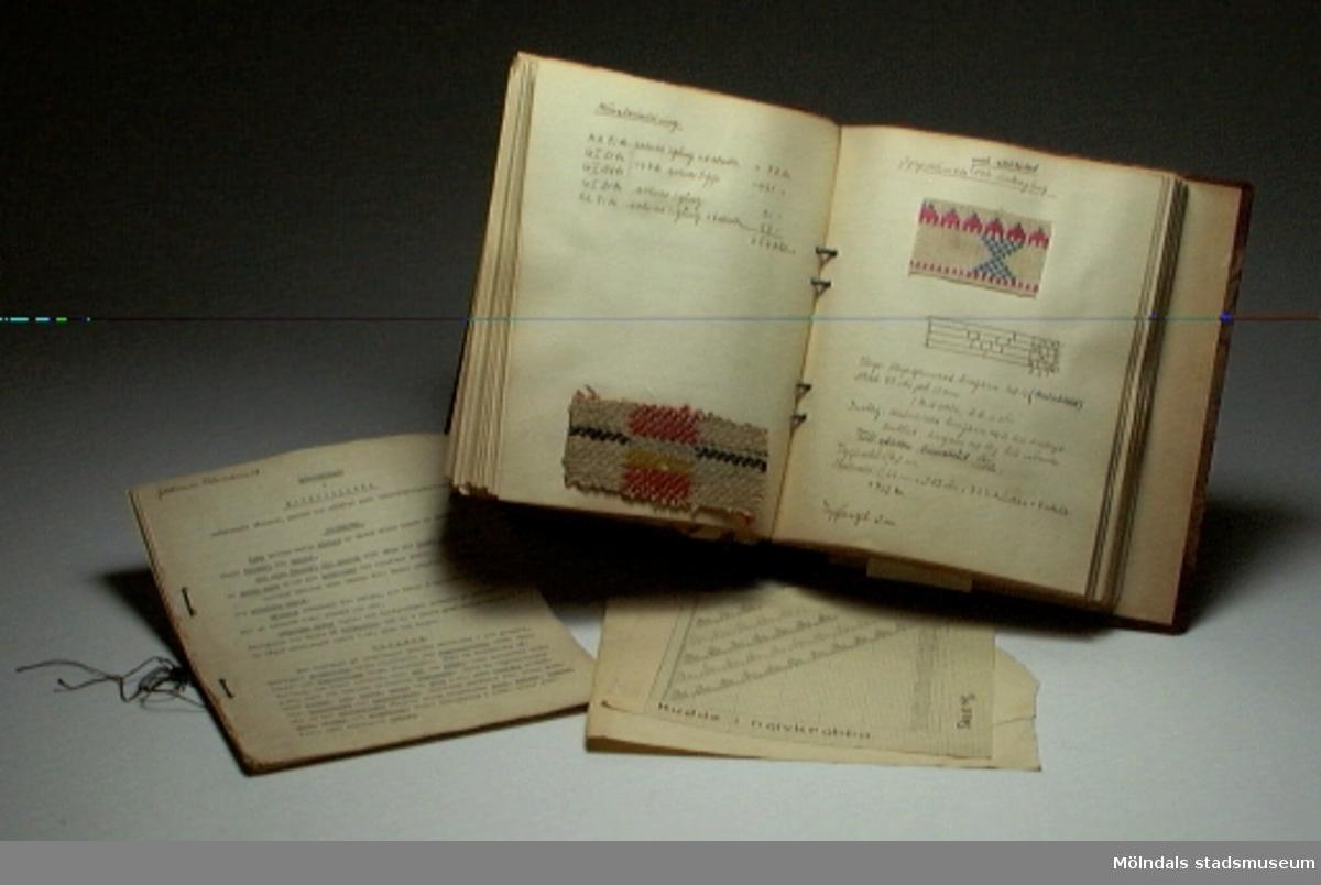 """Pärm med titeln """"Praktisk vävbok"""", med exempel på olika vävtekninker, som illustreras med textila vävexempel. Pärmen innehåller också ihopbundna pappersark med titeln """"Anteckningar i materiallära"""", samt emellanåt lösa papperslappar."""