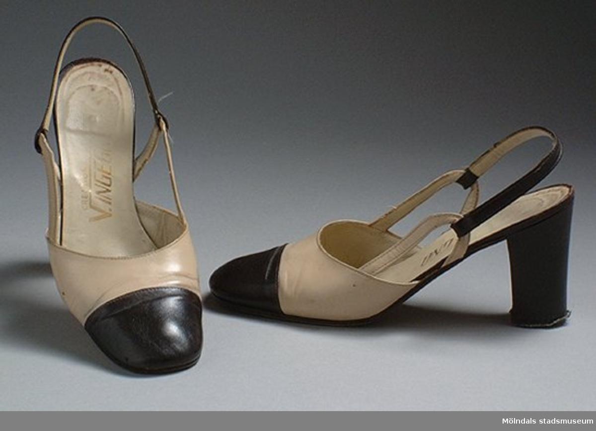 Öppen sko i brunt och beigt skinn. Har ett band vid hälen och hög klack.Det finns också tillhörande klänning, hatt och tygkasse: invnr. MM03323, MM03324, MM03326.Måtten:Stl 37, längd 250 mm, bredd 75 mm, höjd 80 mm (klack).