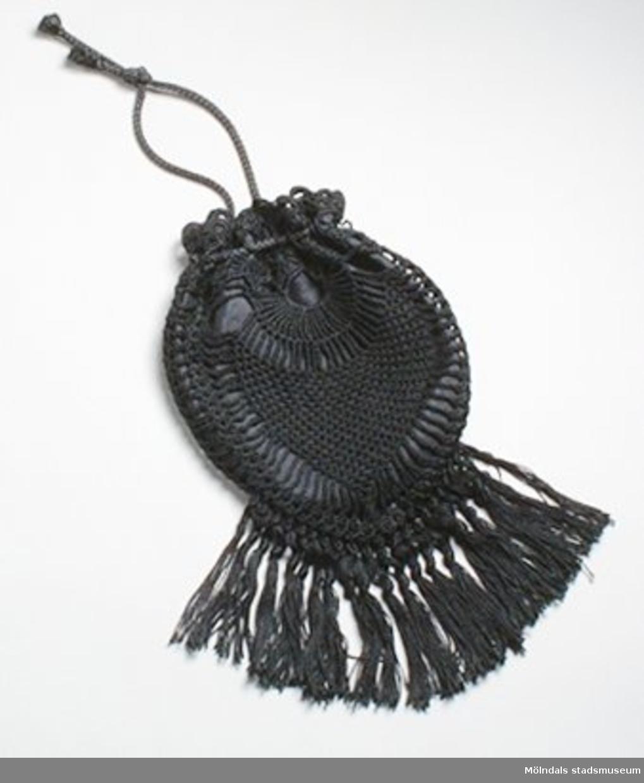 """Handvirkad svart teaterväska med fransar. Har sidentyg som foder och """"dragsko"""" som öppning. I väskan hittade man en papperslapp med orden: """"Handvirkat av Gudmor, I början av 1900-talet, Margits teaterväska"""". Man hittade även muddar: invnr. MM03363.Det finns också tillhörande klänning och hattar: invnr. MM03330, MM03332, MM03333.Måtten:Bredd 150 mm, höjd 330 mm."""