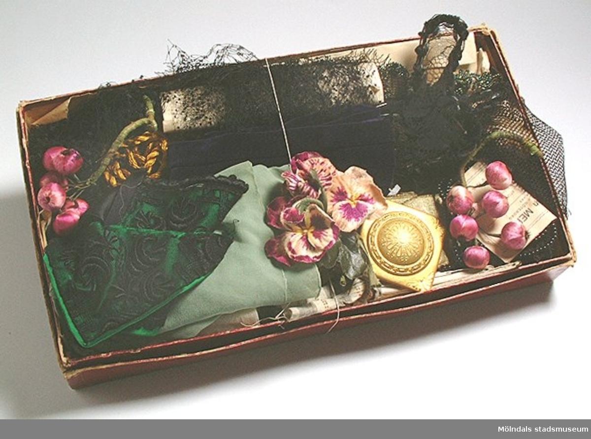 Låda med olika slags klänningsgarnityr såsom flor, blommor och band.