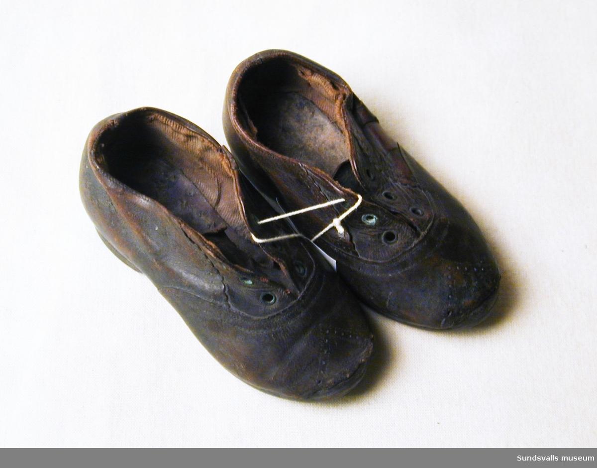 Något mönstrade barnskor i brunt läder. Fodrad invändigt. Tre hål att trä skonsnörena i.