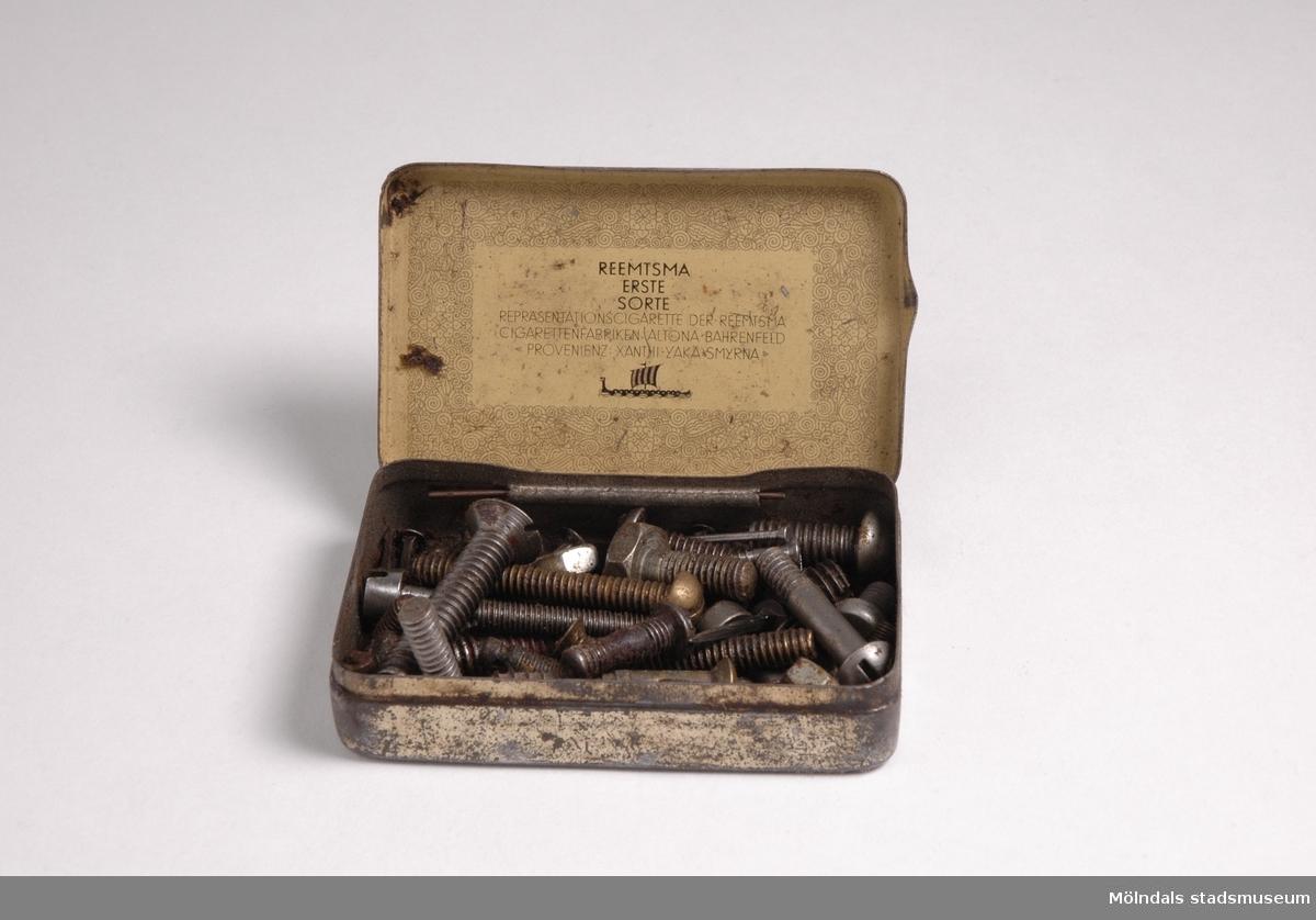 Plåtask med skruvar, muttrar och spik i olika storlekar.Redskap och verktyg kommer från Lindströms snickeri (Gamla Riksvägen 81, Ekebacken). Här byggde John Lindström från Lindome ett boningshus och snickeriverkstad 1928. Han öppnade ett snickeri som specialiserade sig på köksbord. Borden levererades till en grossist i Göteborg. Som mest tillverkades 50-60 bord i veckan. Borden hade ben av björk och resten var av furu. Han gjorde även andra möbler på beställning. Till hjälp hade John ett par anställda.