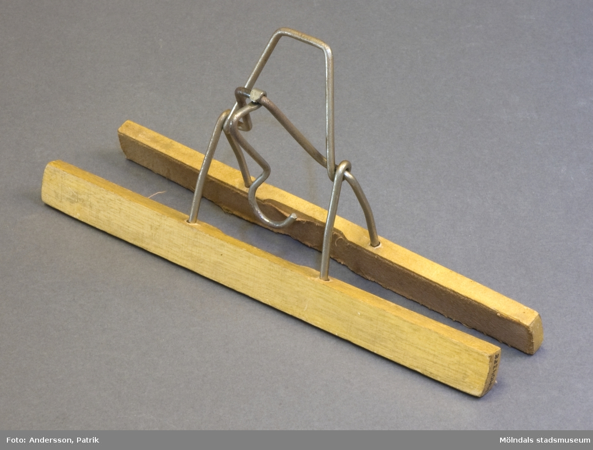 Byxhängare eller byxklämma. Byxans benslut kläms fast mellan två tygfodrade trälister, vilka kläms ihop med en metallkrok.