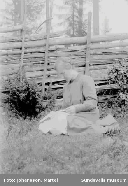 Kvinna sitter framför gärdesgård och ev läser en bok.