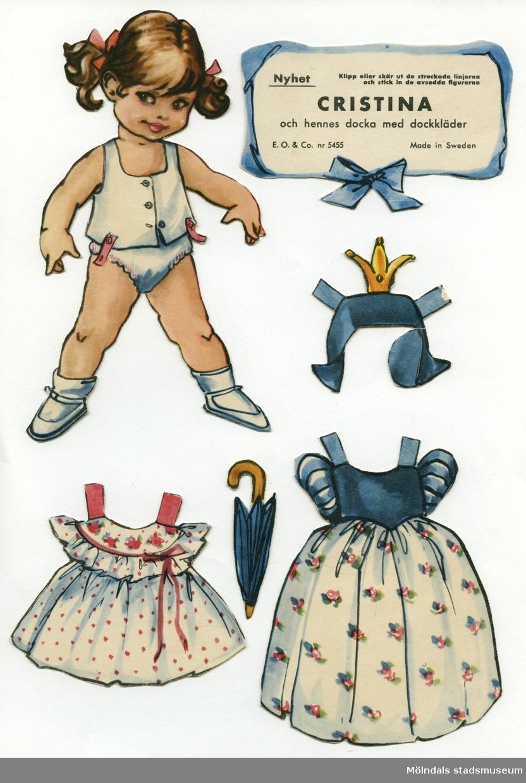 """Pappdocka med kläder och tillbehör från 1950-talet. Docka och kläder är märkta """"Cristina"""" på baksidan - dockans namn. Dockan föreställer en flicka med brunt hår i tofsar, iklädd underkläder, strumpor och skor. Garderoben består av fem klänningar, en prinsessklänning med tillhörande huvudbonad, hängselbyxor, pyjamas, samt ytterkläder. I materialet ingår även tillbehör, såsom paraply, hårborste, blomsterkorg, väska och dockvagn. Pappdockan har dessutom en docka med egna kläder och tillbehör (MM 04662). På en liten skylt av papp står det: """"Cristina och hennes docka med dockkläder, E. O. & Co. nr 5455, Made in Sweden"""". Texten är inramad av blått band och rosett. Docka och kläder förvaras i ett brunt kuvert, ursprungligen från Uppbördesverket, Göteborg (Skatteverket)."""