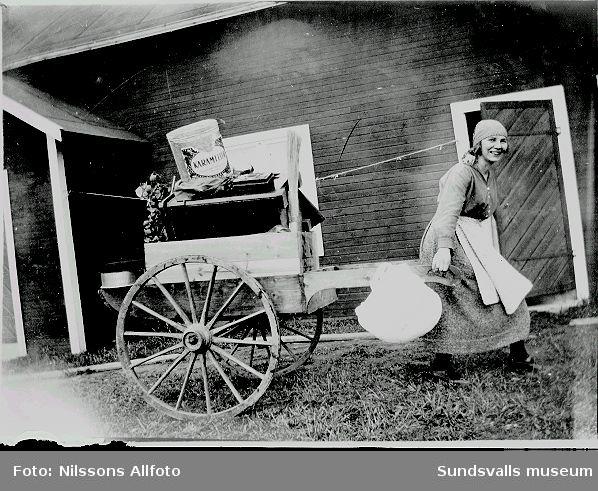 Kvinna drar en kärra med varor.
