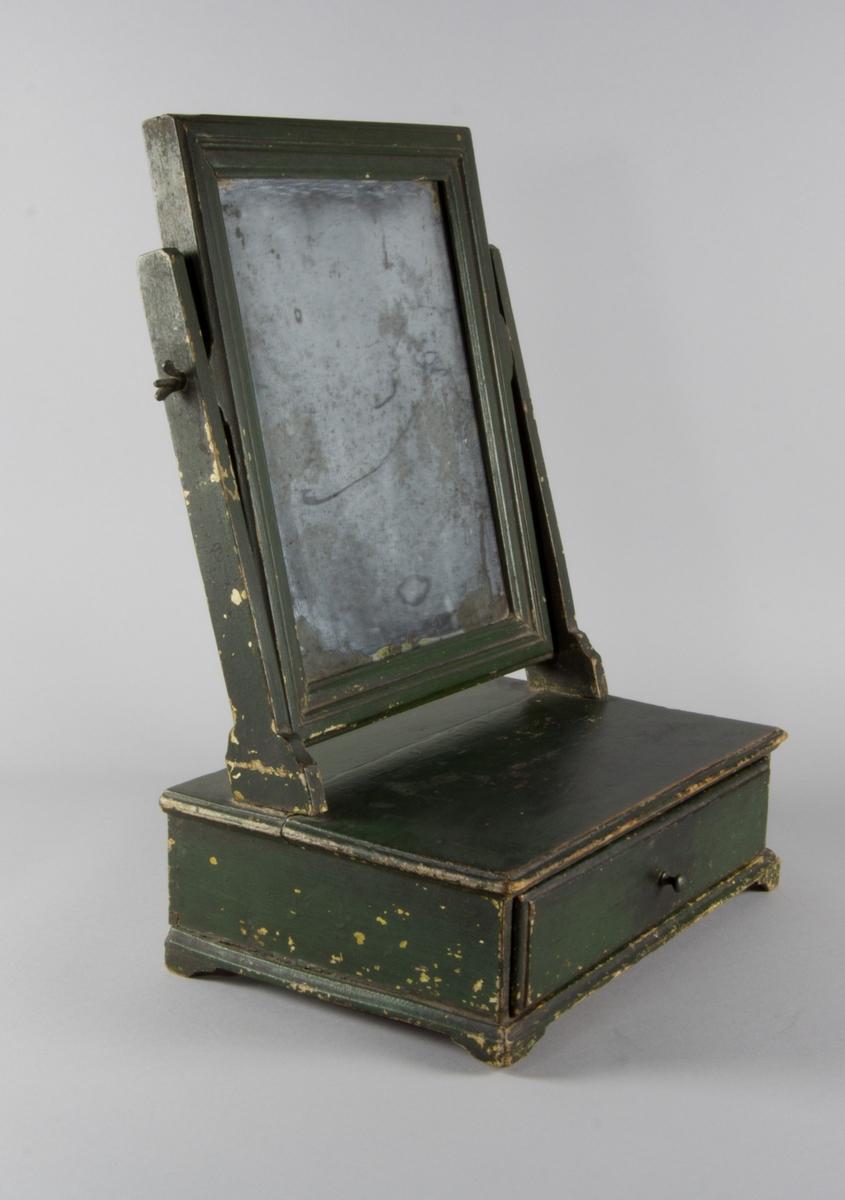 Toalettspegel av trä, grönmålad, med kvadratisk spegel löst monterad med muttrar vid två raka ståndare och med låda med knopp.