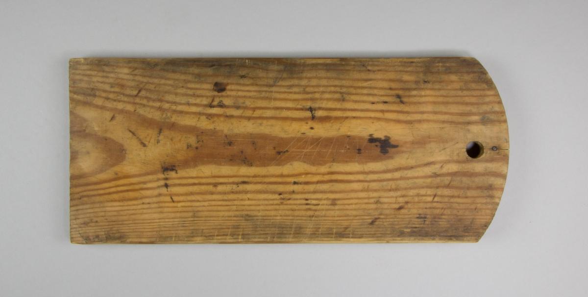 Skärbräda av furu. Rektangulär med en svängd kortsida med hål för upphängning.