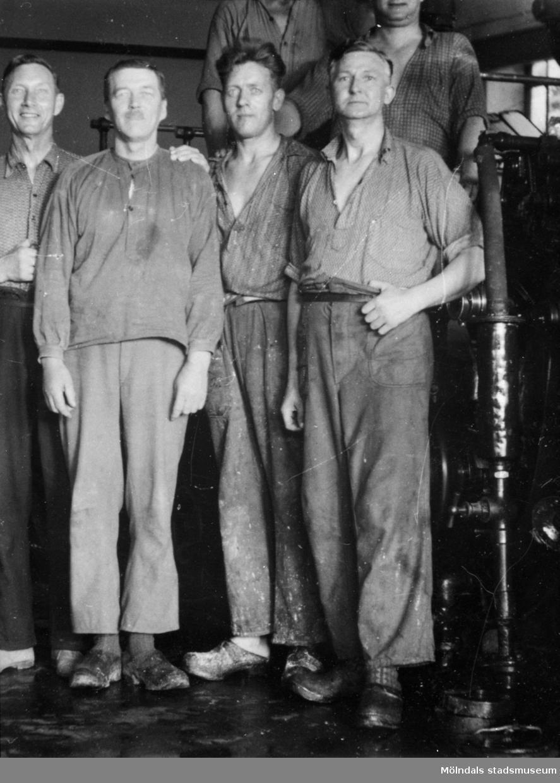 Papyrusarbetare uppställda framför maskinerna inuti fabriken ca 1930. Mannen till höger är Artur Svensson, född 1892.