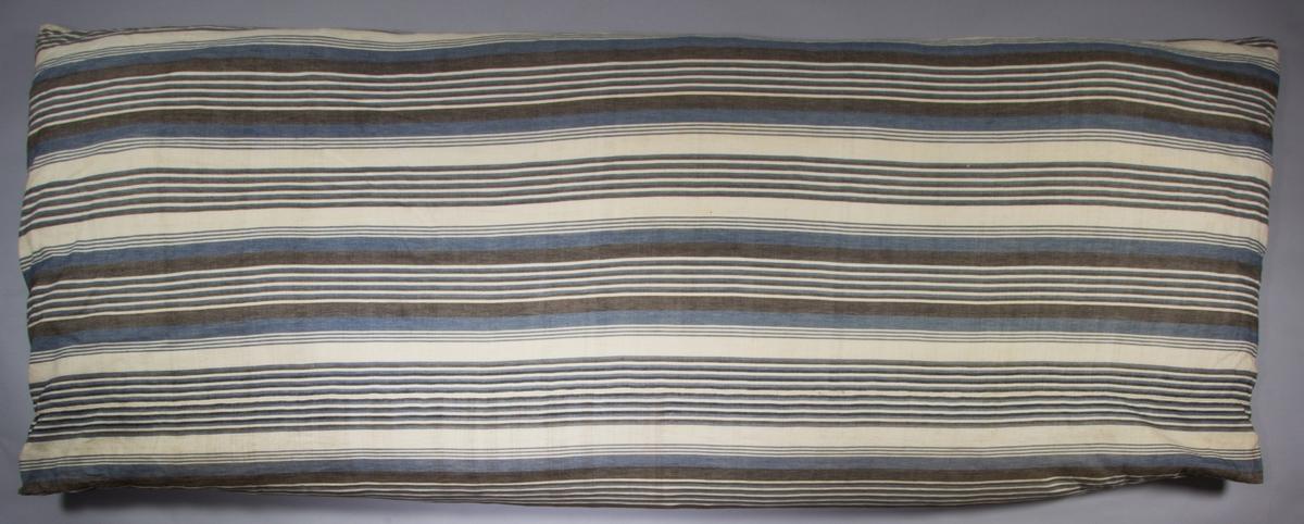 Bolster, tillverkat av troligen handvävt linnetyg, i en bred spetskypertsbindning. Varpen i kärnrandning,  med ljus botten och ränder av blått, brunt och något svart. Det svarta finns i en sida bara och verkar vara utfyllnad, för att det blå garnet inte räckt till.  Enfärgat ljust inslag. Handsytt. Fyllning: fjäder.