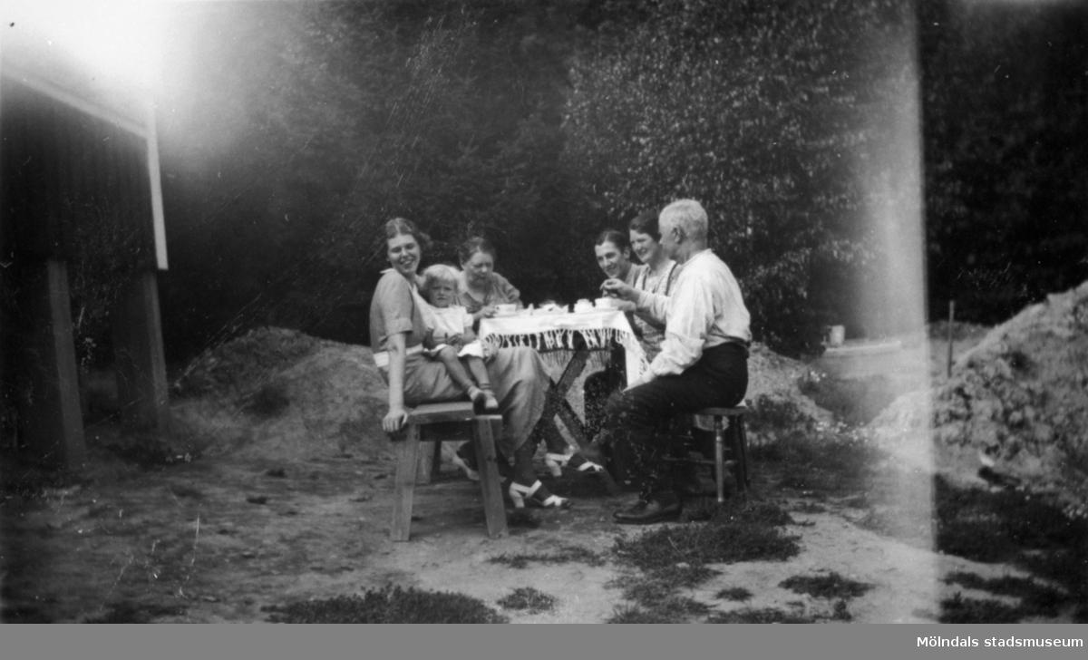 """Kvinnor, män och ett barn vid ett dukat kaffebord utomhus. Bilden märkt: """"Från Kållered"""". 1930-tal."""
