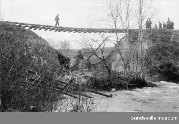 Statsbanan mellan Sundsvall-Ånge hänger fritt i luften sedan banvallen försvunnit i samband med vårflodens härjningar 1919. Fotot taget från Grönborgssidan.