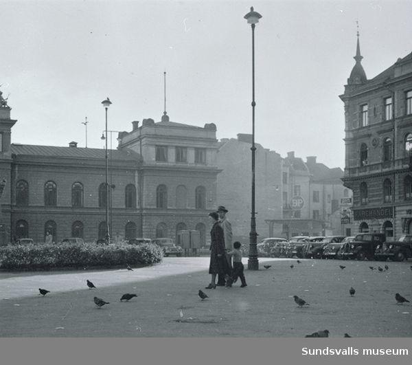 Flanörer på Stora Torget. Stadshuset syns i bakgrunden. En BP-station ses skymta t h efter Kyrkogatan.
