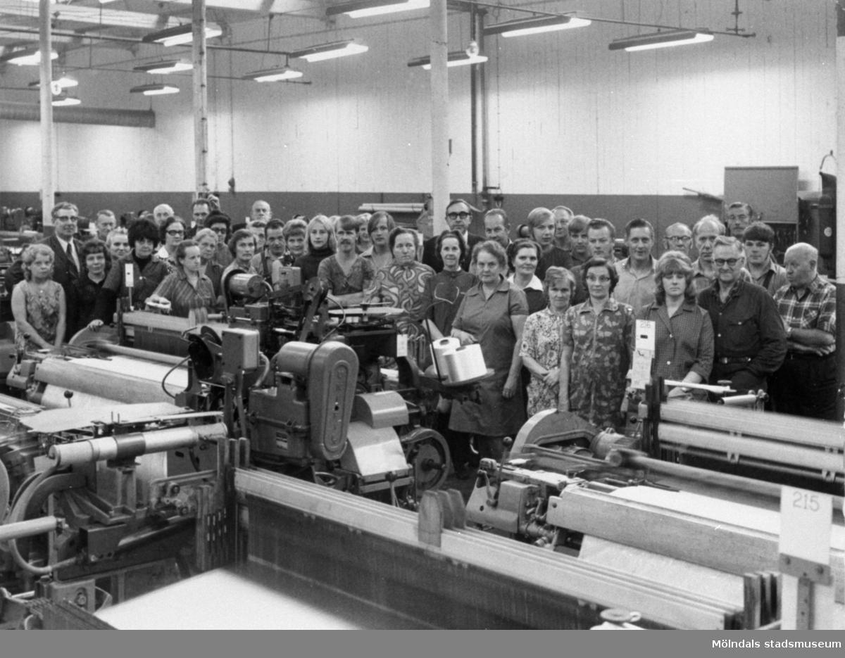 """Arbetare vid Krokslätts fabriker i Mölndal år 1971. Text på bildens baksida: """"Sista metern väv (nylontaft) slutvävdes fredag 10 dec 1971 kl 10.48 av Linnea Dahlryd""""."""