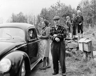 Greta Pettersson och Per Persson i Södra Havhult, får dagens post. Vikarierande bilåkande lantbrevbäraren Gert Stjernqvist, på linjen Lönsboda-Duvhult.  Foto maj 1961.