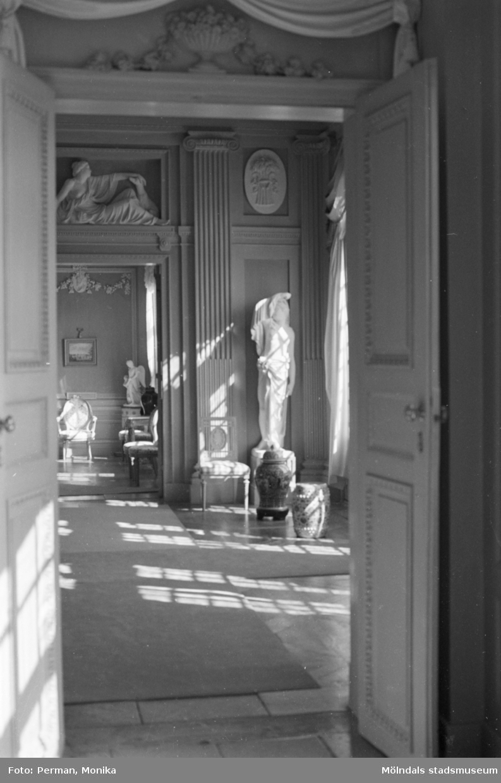 Dokumentationsbilder från Gunnebo slott våren 1992. Inredningsmiljö, konstföremål och möbler av varierande slag. Här ses en korridor av rum varav det mittersta har en staty och höga vaser.