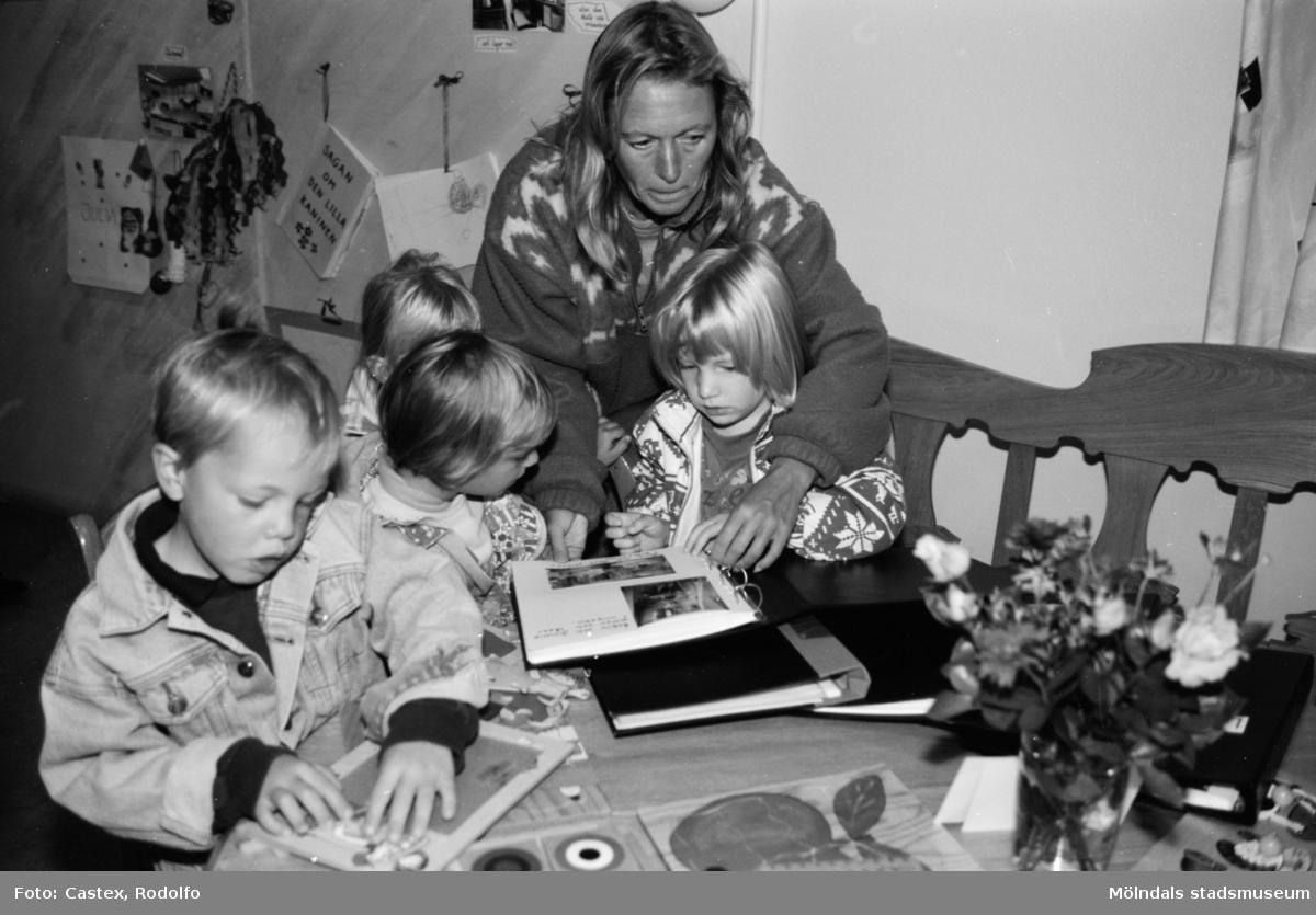 Fyra barn pysslar eller tittar i fotoalbum tillsammans med en vuxen person. Utställningsvernissage av och om Katrinebergs daghem på Mölndals museum 1993-09-10.