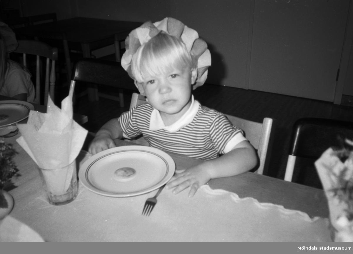 En liten ljushårig pojke sitter inomhus vid ett dukat bord. Han har armarna liggandes på bordet och ser lite ledsen ut. På bordet ligger en duk, bestick, ett glas innehållande en servett samt en tallrik med en kaka på. På huvudet har han någon slags virad girland. Möjligtvis i samband med midsommarfirande på Katrinebergs daghem.