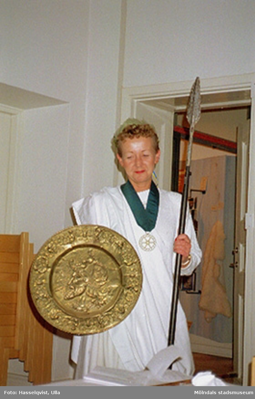 Pia Persson utklädd i toga, hållandes ett spjut och en vapensköld i var sin hand. Detta i samband med avtackning av receptionist Kim Linder på Mölndals museum 1994.