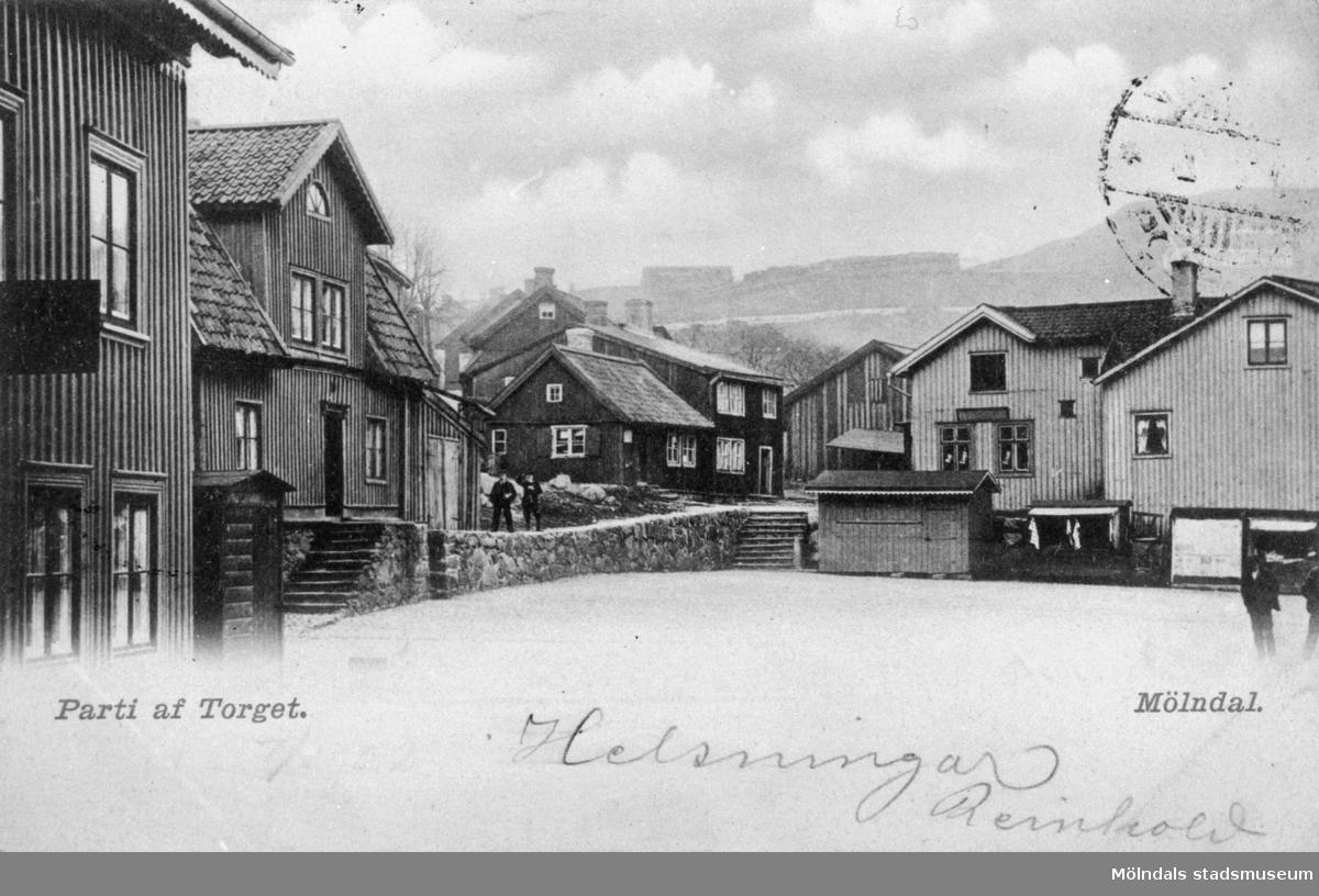 """Vykort """"Parti af Torget. Mölndal"""", med handskrivet Helsningar Reinhold, postat den 7/1 1902. Man ser Gamla torget från sydväst. Till höger ses Kvarnbygatan 39, därefter följer """"Såget"""", på vars plats senare Gamla stadshuset (Kvarnbygatan 43) byggdes. Därefter ses Grönsiskas hus och Malmgrens (Kvarnbygatan 45)."""