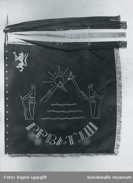 """Kopia av Bataljon lll:s fana. Bataljon llls fana som tillverkades till hemresan i maj 1945, och kom till anvendning först i Trondheim, enligt uppgift från Willy Svendsen , Hudiksvall. Fanan finansierades bl a med överskottet från försäljningen i """"markan"""" i fritidsbaracken. Fanan formgavs och tillverkades av en kvinnlig konstnär i Södertälje."""