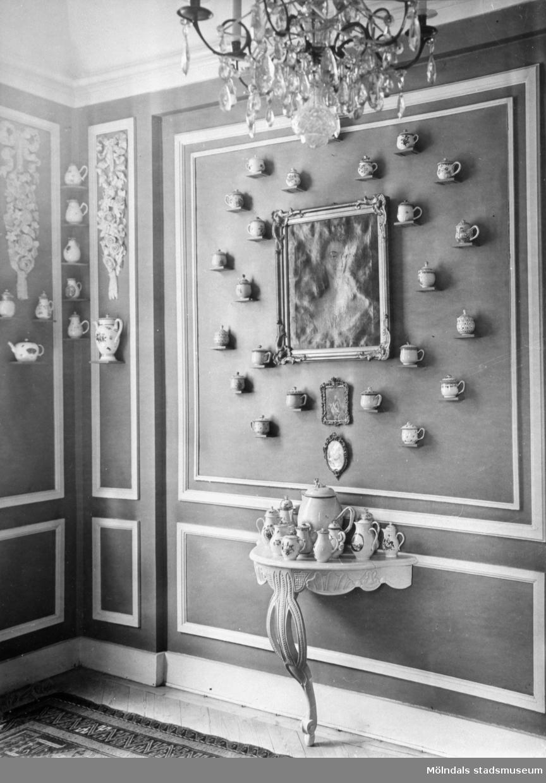 Rikt dekorerad vägg med flertalet porslinsföremål. I taket hänger en ljuskrona och på golvet står ett väggbord. Gunnebo slott.
