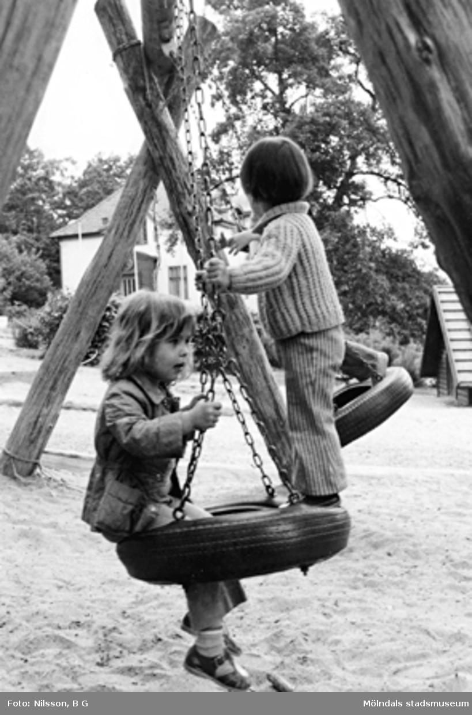 Två barn tillsammans på en gunga. Holtermanska daghemmet 1973.