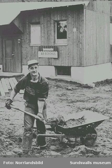 Man i färd med markplaneringsarbete under bygge av typhus i trä från leverantöreren AB Borohus.