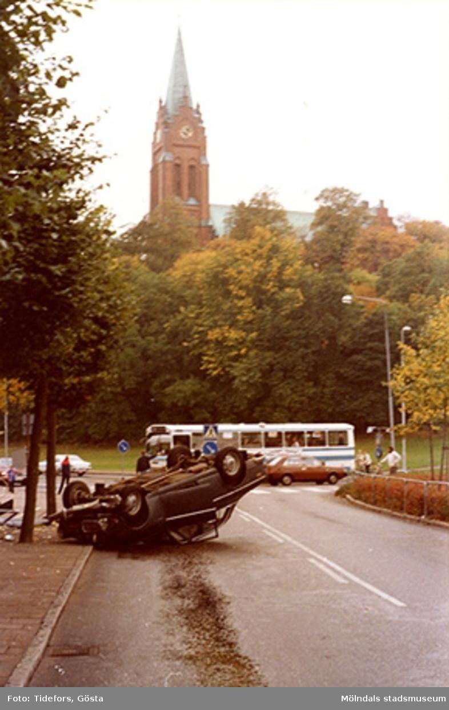 Olyckan har skett innan korsningen Häradsgatan och Tempelgatan mot Fässbergs kyrka, 1970-tal. I bakgrunden ses en buss samt människor som väntar vid övergångsställe.