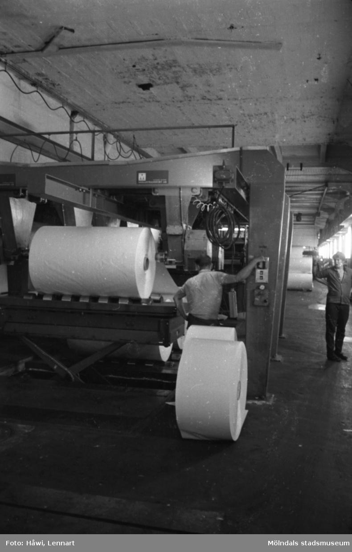 Män i arbete vid maskin. Antagligen Voldemar Mei med ryggen vänd mot kameran. Rullar läggs i klippen och klippta ark kommer ut på andra sidan av maskinen. Klipp 5 (fabrikat Masson/Mason & Scott), byggnad 10. Papyrus i Mölndal, hösten 1970.