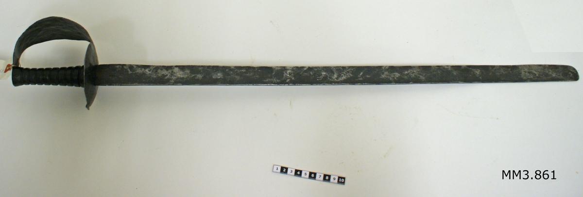 Huggare, utan balja, imitation av MM 3858. Fästet består av trä och parerplåten av tunnplåt, svartlackerade. Klingan är eneggad och smidd av järn.