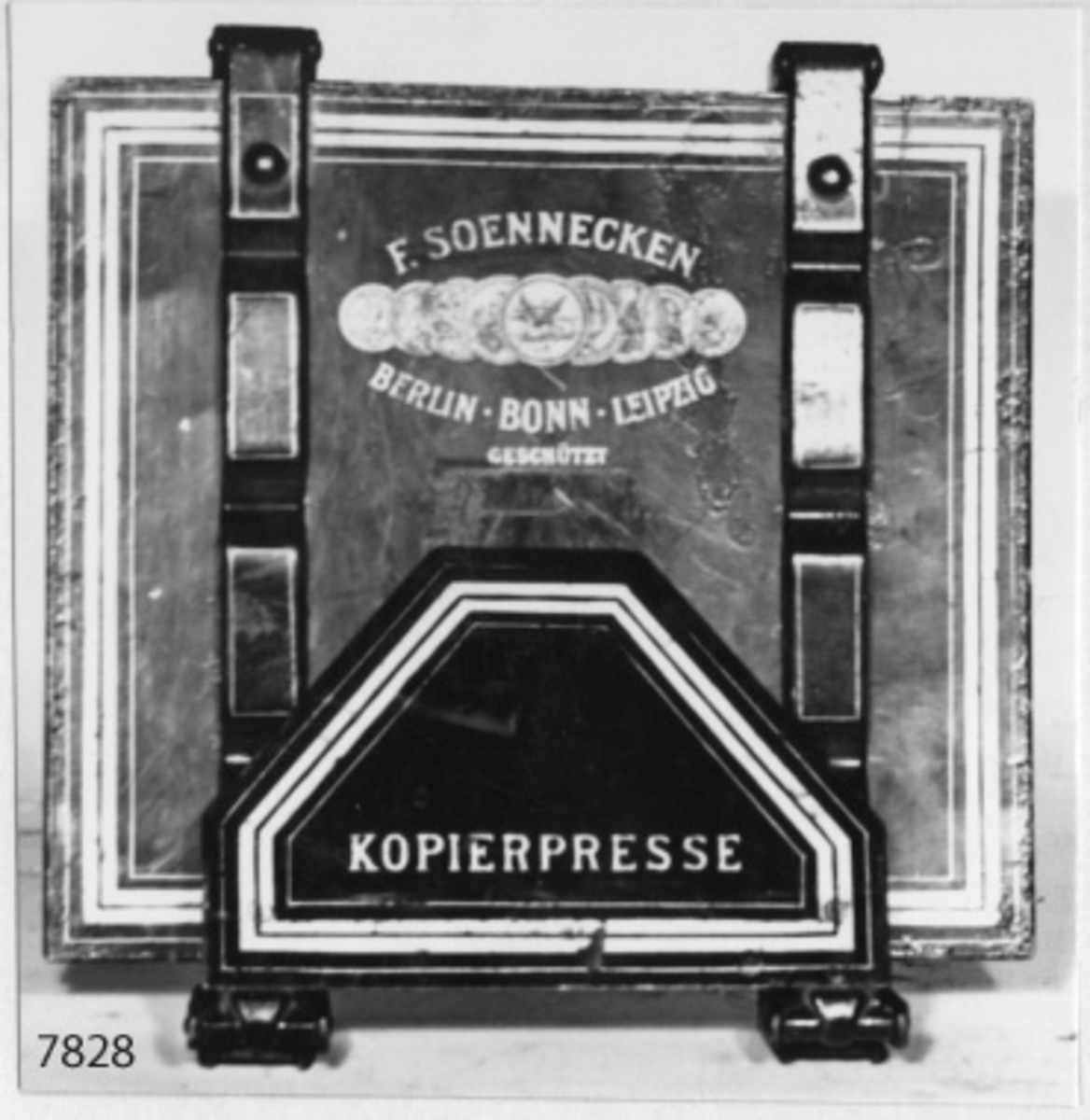 Kopiepress av järn, svartlackerad med ränder i gult. Tysk tillverkning från 1800-talets senare del. Pressen rektangulär. Märkning: F. Soennechen samt medaljer och fabriksmärke, därunder: Berlin x Bonn x Leipzig Geschützt. No 1.