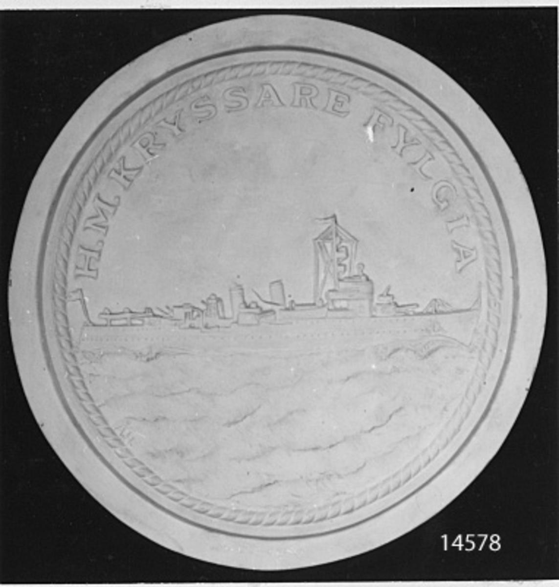 Minnespenning. Originalmodell. På framsidan: Kryssaren Fylgia. Text: HM Kryssaren Fylgia.