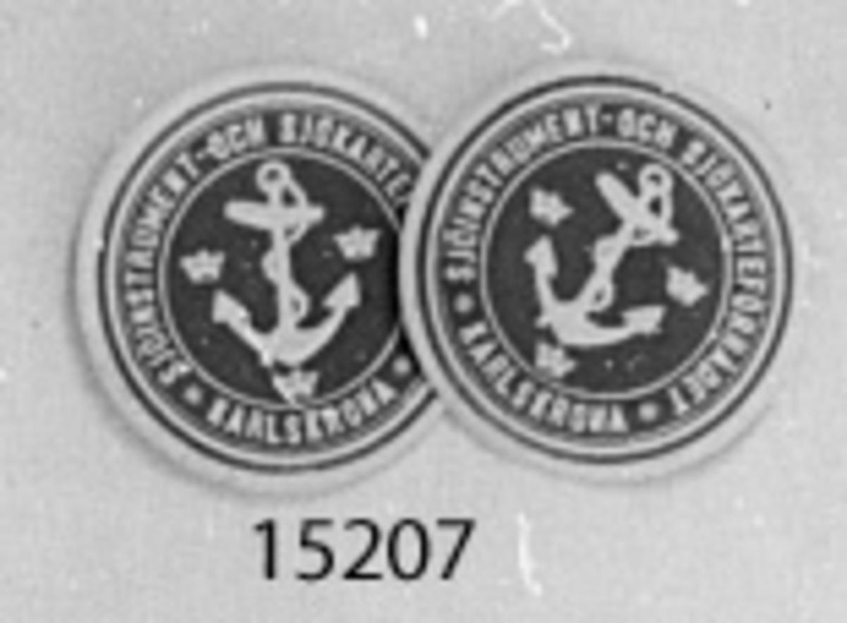 Munlack cirkelrund pappersbit med blå ovansida, med figur och text i vitt. I mitten ett ankare och tre kronor, en på vardera sida om ankarstocken, en nedanför. Runt ankaret texten: Sjöinstrument- och sjökarteförrådet, Karlskrona. Baksidan gummerad.