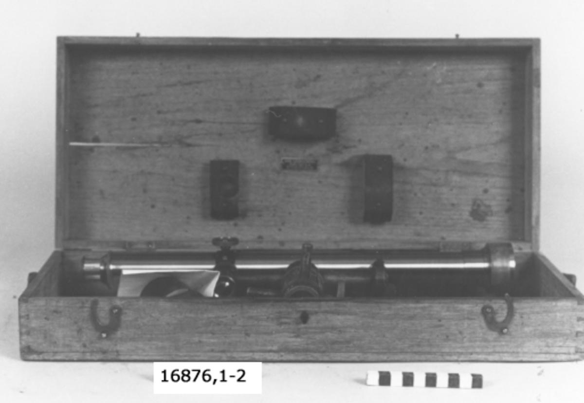 """Låda av fernissad ek med två hakar för stängning av locket. Bärrem av läder. På framsidan bricka med texten """"BR1"""". Invändigt träklossar som stöd för instrumentet samt bricka med texten """"Axel Ljungströms fabriks AB Stockholm"""". I lådan finns litet verktyg som är en kombination av två skruvmejslar och två skiftnycklar samt mässingsrör som passar till kikarens rör som bländskydd."""