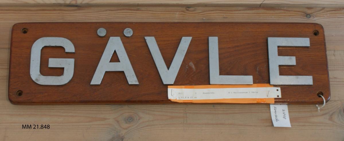 Namnbräda av teak, fernissad. Bokstäver av vitmetall: Gävle. X 13.