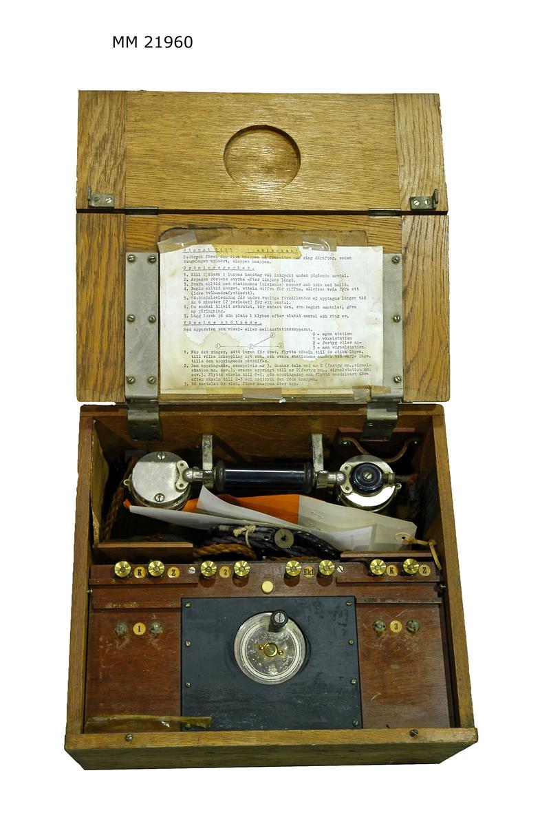 Lådtelefon med inbyggd växel för tre anslutningar. Användningsinstruktion i locket, samt två fotografier. X 619.