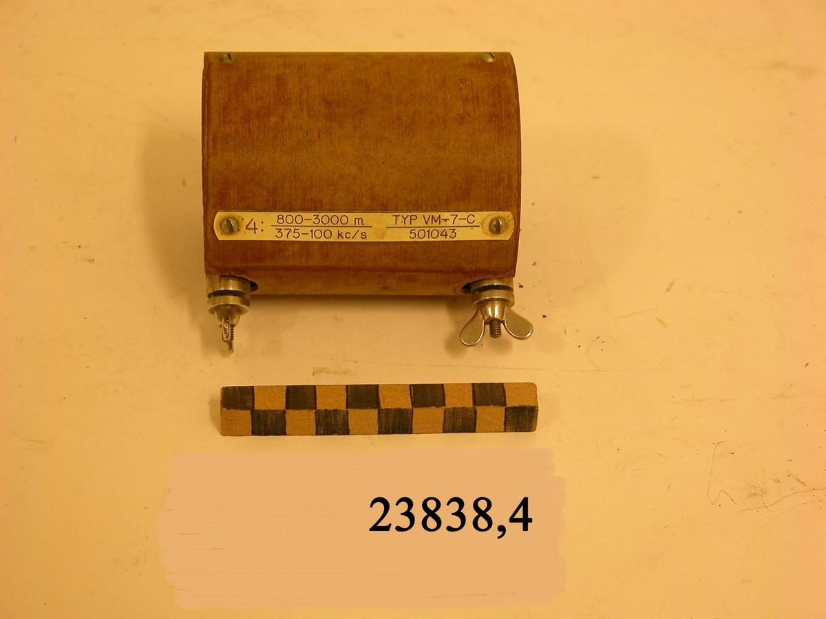 Ljusbrun cylinder med dubbla väggar och två skruvar av metall med vingmuttrar. På cylindern en fastskruvad bricka av plast med text : 4: 800-3000 m. 375-100 kc/s. TYP VM-7-C. 501043.