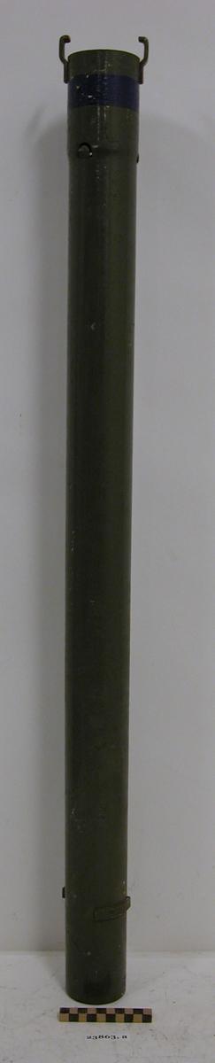 """Grönlackerat metallrör med handmålat blått runtgående fält= övningsrörladdning (över tidigare gulmålad ring). Röret har den stansade texten """"RÖRLADDNING m/41-44 STRIDS-"""". Rörets ena ände har bajonettlås bestående av två utåtriktade beslag för fästande av ytterligare ett rör eller en konformad spets. Nedanför finns två beslag för låsning av den påmonterade delen. Andra änden har två beslag för låsning av den påmonterade delen."""