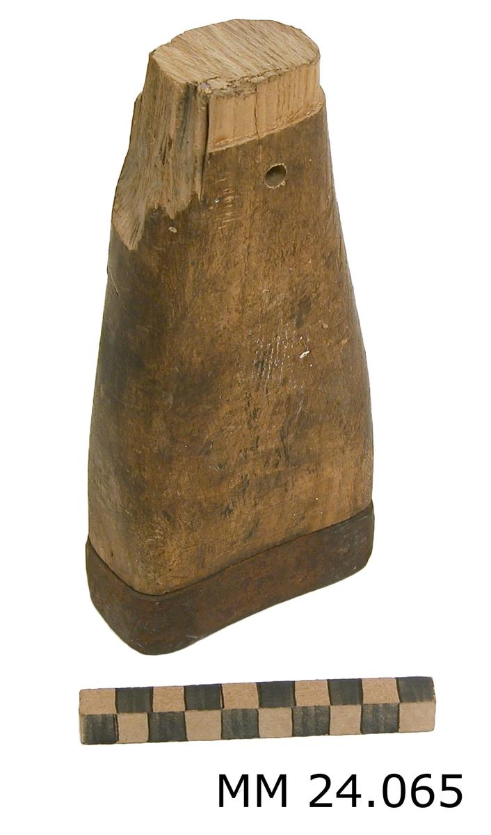Rektangulär träkolv med omslutande band av järn på nederdelen, överdelen saknar band. Träkolven är avsmalnande mot överdelen. I överdelen finns ett genomgående hål.