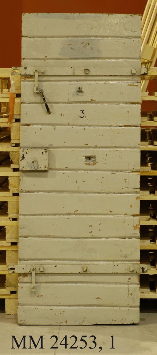 Sannolikt dörr med karm från en av cellerna i arrestlokalen i cellbyggnaden på NV. Losstagen i samband med renovering. Dörren tidsenlig, byggnaden från 1920-talet. Dörr och karm gråmålade, färgen dock flagnande.