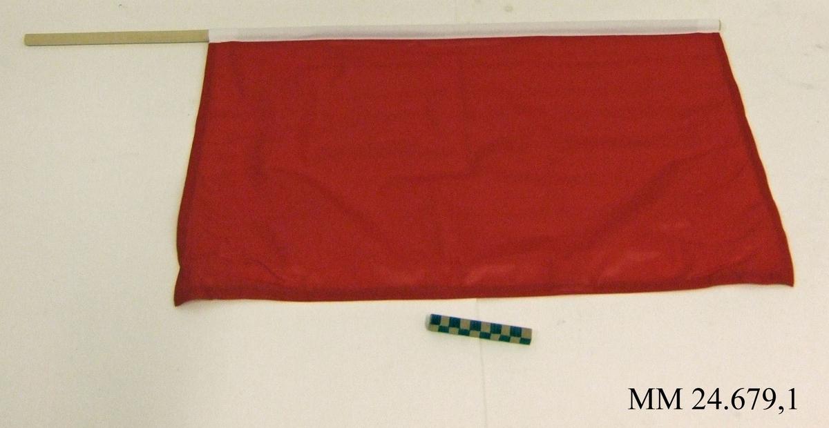 Manöverflagga på stång av trä. Flagga av röd nylon med vitt lik trätt över rundstaven och fäst med häftklammer. Flaggan ligger i påse tillsammans med fem andra flaggor, sk. manöverflaggställ.