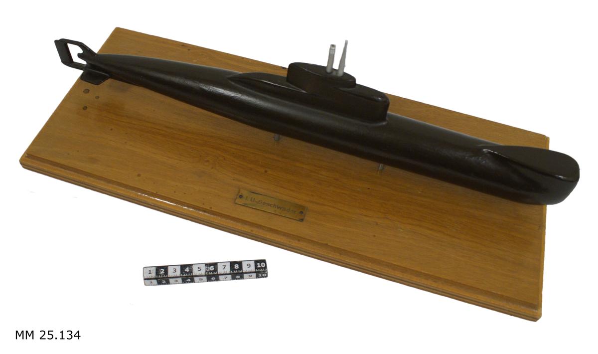 """Ubåtsmodell av metall. Ubåten är målad i en mörk svartbrun ton. Färgen är ganska grovt påmålad, det syns att den tjocknat och runnit på vissa ställen. I ubåtens för sitter en upphöjning, sannolikt en dom för sonaren. På tornet, som är i tre nivåer, sitter två periskopmaster. Dessa är målade i en ljusgrå färg. I ubåtens akter sitter ett fixerat roder. Ingen propeller, men sannolikt har det inte funnits någon på modellen. Ubåten sitter fast på en fernissad träplatta med profilerade kanter. Plattan består av flera skivor limmade mot varandra. Ubåten sitter med två grå metallpinnar som sitter skruvade i plattan och sedan går in i ubåtens skrov på undersidan. På träplattan sitter en metallbricka fastspikad. Text på brickan: """"1. U-Geschwader"""". På träplattans undersidan sitter en klisterlapp med texten: """"Zur Erinnerung an den Besuch des 1. U. GESCHWADERS in Trelleborg 29.8.-1-9- 1975"""". På klisterlappen har någon skrivit sin namnteckning i blå penna, men denna är oläslig."""