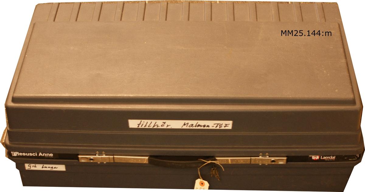 """Grå resväska med hjul. Märkt med svart tusch på vit tejpremsa: """"Tillhör Malmen TSF"""". (TSF betyder sannolikt Truppserviceförråd)."""