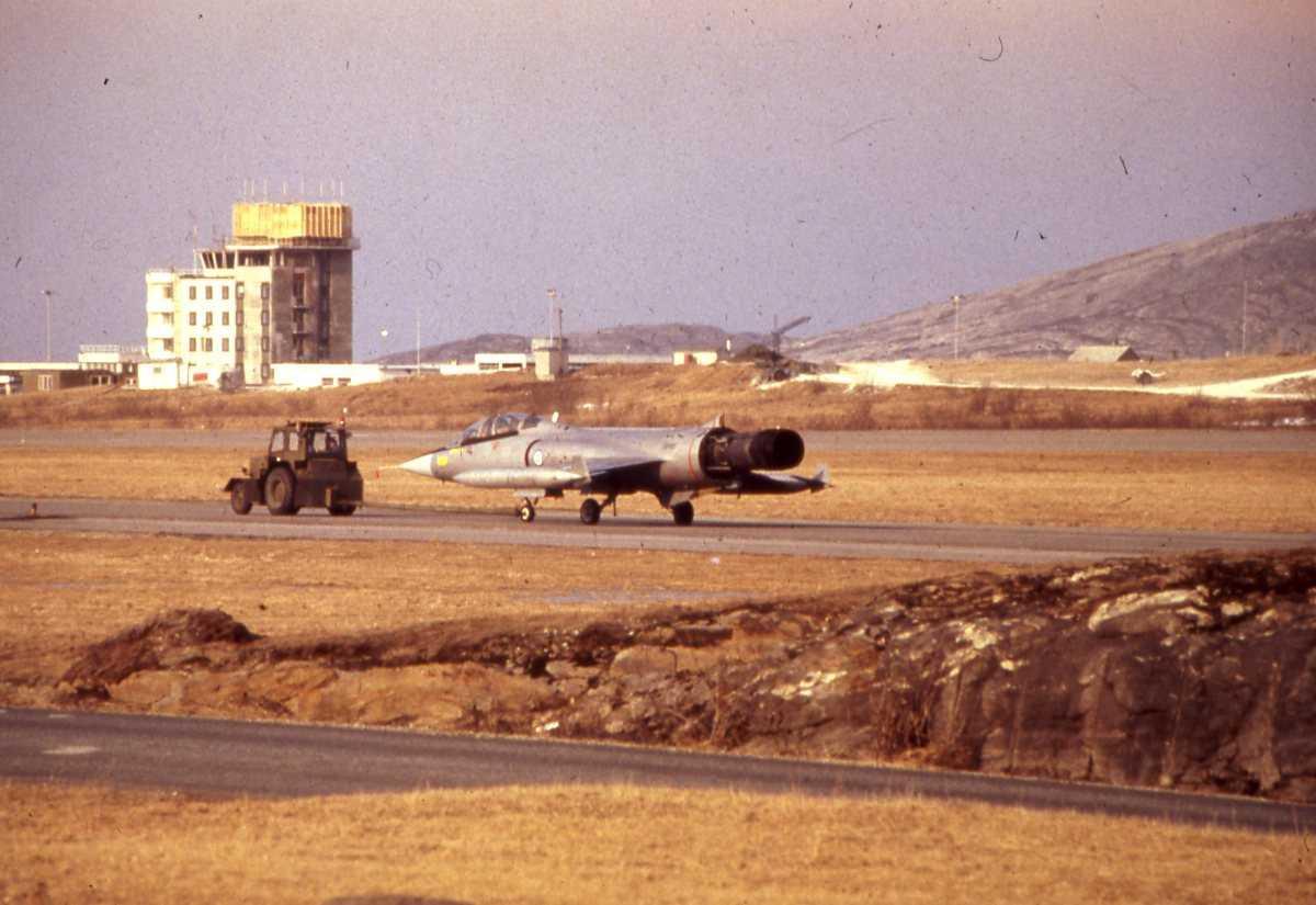 Norsk TF-104G Starfighter som slepes av et militært kjøretøy på Bodø hovedflystasjon. I bakgrunnen sees det nye kontrolltårnet som er i ferd med å bli bygget.