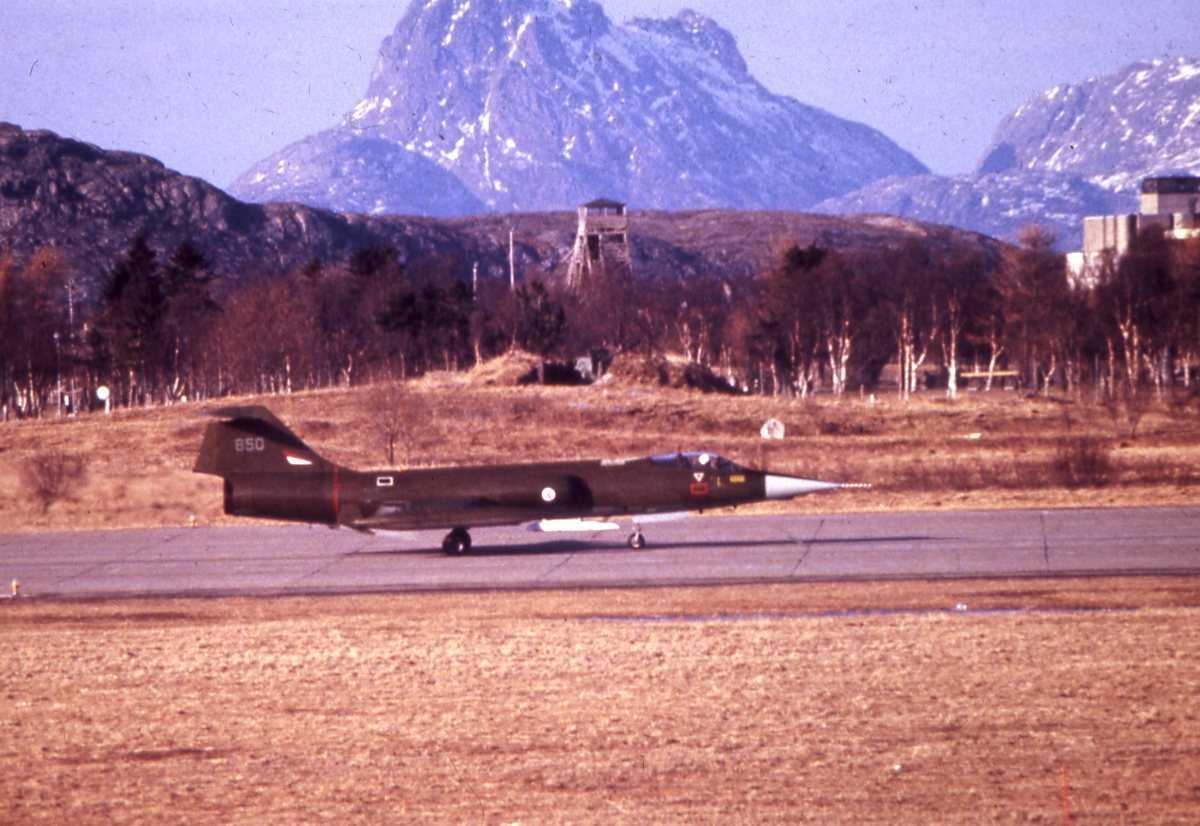 Norsk CF-104G Starfighter som taxer på Bodø hovedflystasjon. Midt i bildet i bakgrunnen sees et av fjelltoppene på Landegode.
